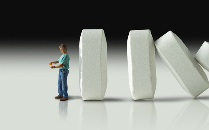 Man standing in front of domino-like pills