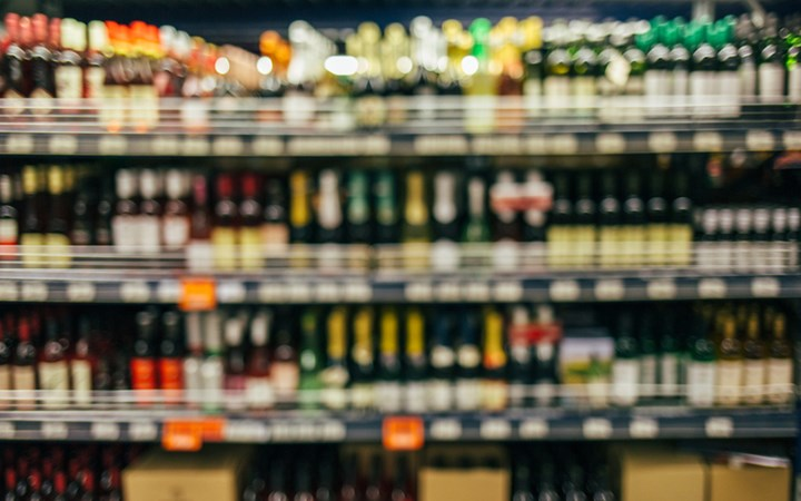 Blurred image of alcohol bottles in a liquor store