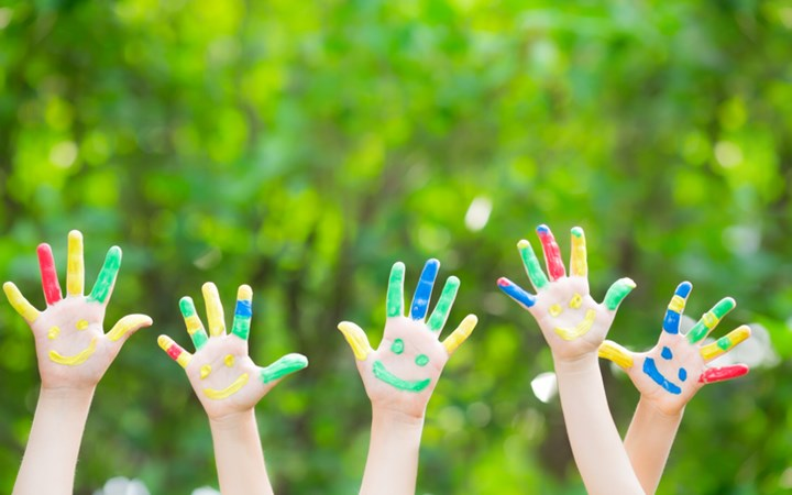 Children with painted fingers raising their hands