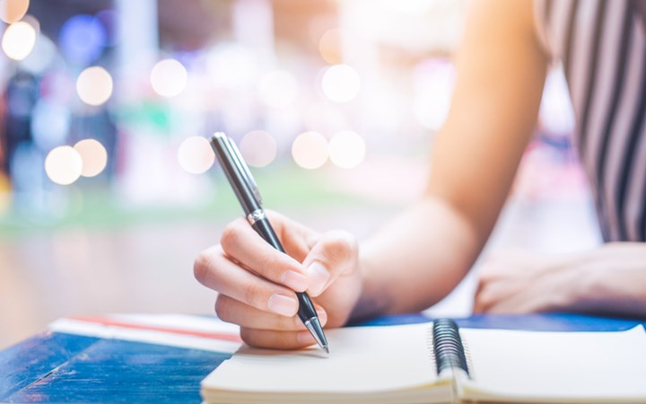 Woman writing in blank notebook with positive lighting in background