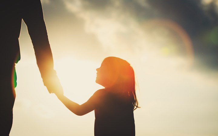 Silhouette of a girl holding adult's hand with sun in background