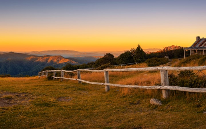 Australian landscape; sunset over mountains with house and wooden fence in front