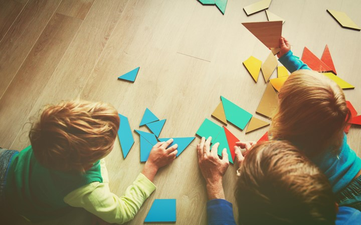 Teacher and kids playing with colourful geometric shapes