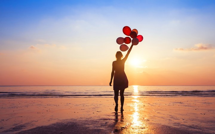 Silhoette of young woman walking into ocean at sunset holding a bunch of red balloons overhead
