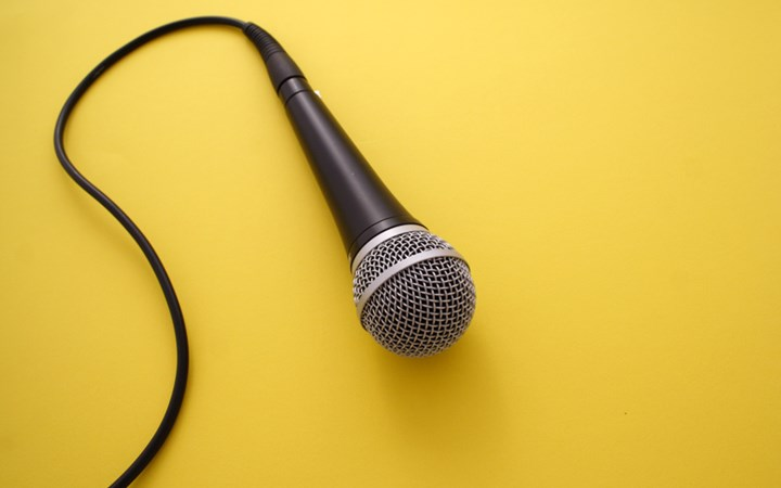 Microphone laying on bright yellow background