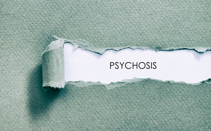Torn paper revealing the word psychosis