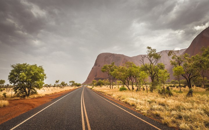 Bitumen road in the National Park leading to Uluru (Ayers Rock), Top Australian Tourist Destination on rainy day