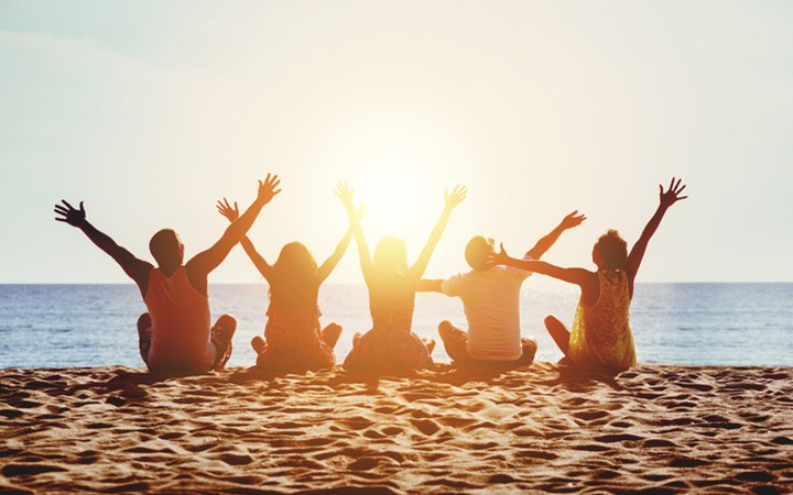 Group of teenagers sitting on beach facing ocean sunset throwing their arms in the air