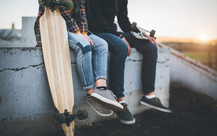 Lower view of two teenagers sitting on concrete wall at skatepark