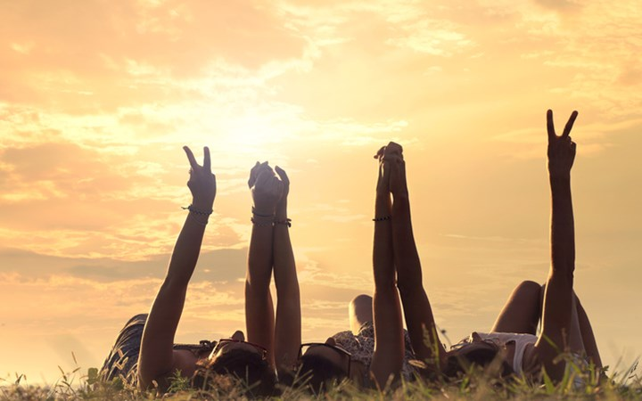 Young people lying in a meadow holding arms up in peace signs, with sunrise in background