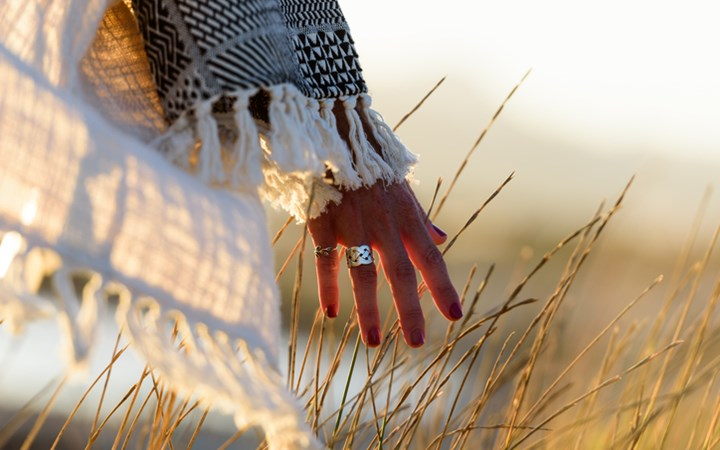 Woman hand caressing grass in field with warm lighting