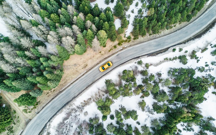 Aerial view of yellow cab driving on windy road through snowy forests