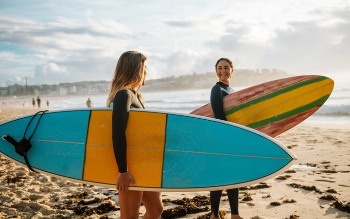 Two female friends at beach holding surf boards