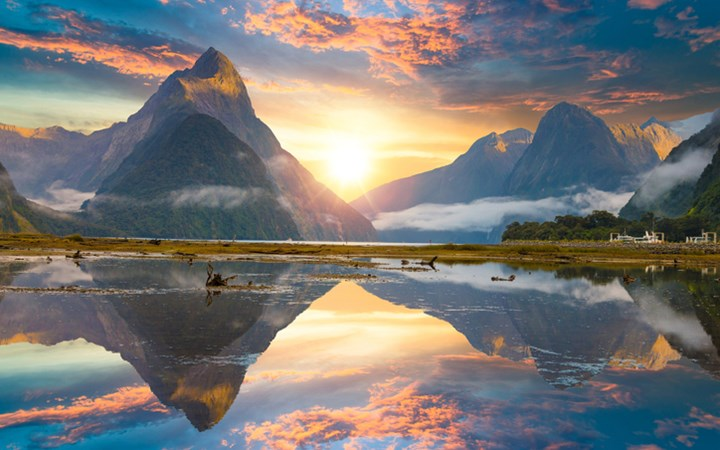 Mountains and sunset clouds reflected onto lake creating mirror image