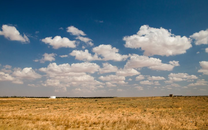 Landscape in Tunisia with flat fields and blue sky with white clouds