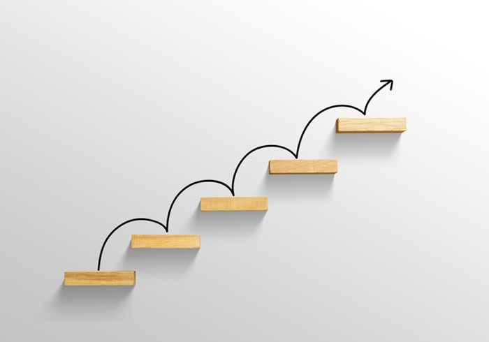 Rising arrow on staircase, moving from one step onto the next in an upward pattern