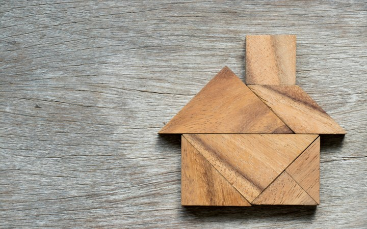 Tangram puzzle in home shape on wood background