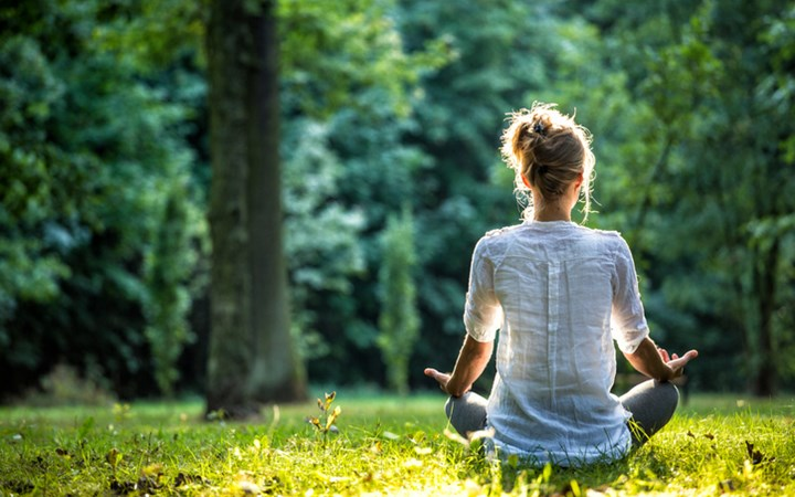 Woman meditating in a green field with back to camera