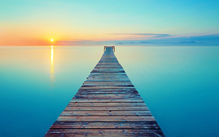 Wooden pier going out into blue ocean with sunset