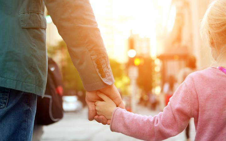 Father holding daughter's hand on busy street