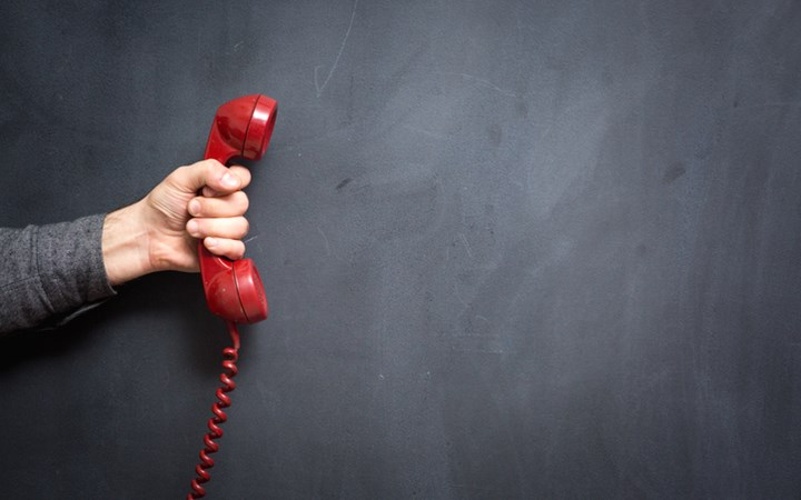 Human Hand Holding Red Telephone with Blackboard in Background