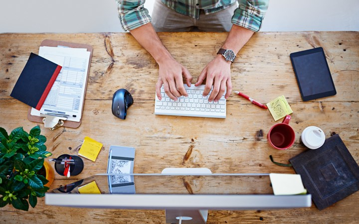 Overhead view of man at wooden table typing on keyboard with office items scattered around him