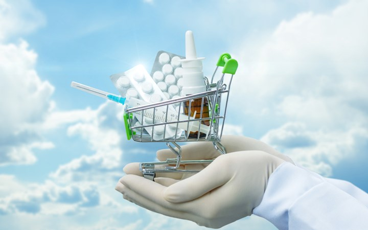 Mini shopping cart in hands filled with medication; blue cloudy sky background