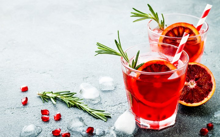 Red cocktail with blood orange and pomegranate. Refreshing summer drink on gray stone or concrete background. Holiday aperitif for Christmas party