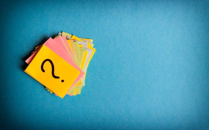 Stack of coloured post it notes with question mark on top